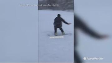 Police officer takes some sledding lessons