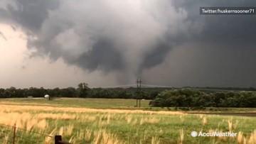 Onlookers film tornado in field