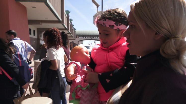 Lesvia Castillo carries her 5-year-old daughter as they walk into the El Paso International Airport
