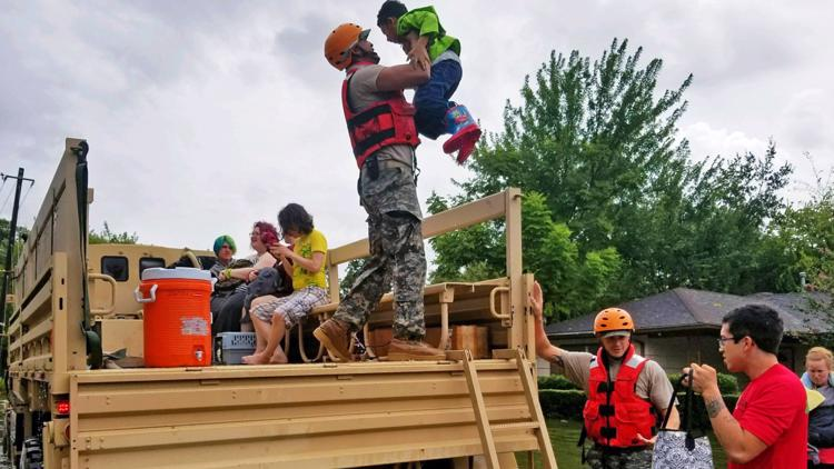 In this handout provided by the Army National Guard, Texas National Guardsmen assist residents affected by flooding caused by Hurricane Harvey onto a military vehicle August 27, 2017 in Houston, Texas.