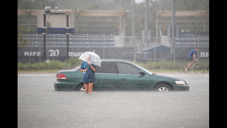 Mari Zertuche walks through a flooded parking lot on the campus of Rice University afer it was inundated with water from Hurricane Harvey on August 27, 2017 in Houston, Texas.