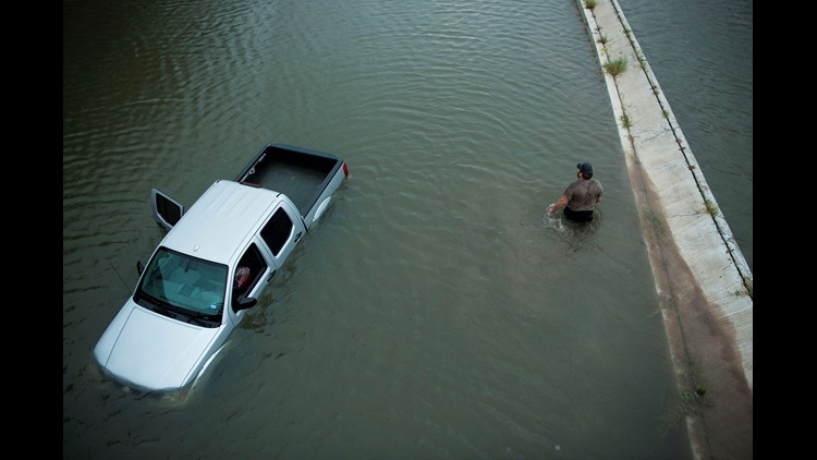 A truck driver walks past an abandoned truck while checking the depth of an underpass during the aftermath of Hurricane Harvey August 28, 2017 in Houston, Texas.