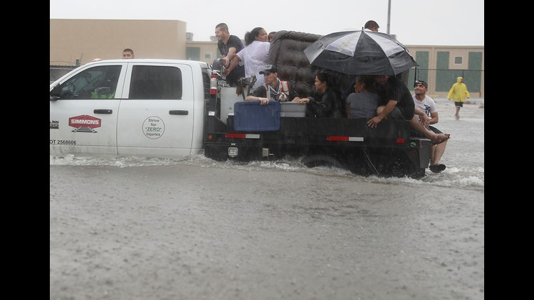 People use a truck to evacuate their homes after the area was inundated with flooding from Hurricane Harvey on August 27, 2017 in Houston, Texas.
