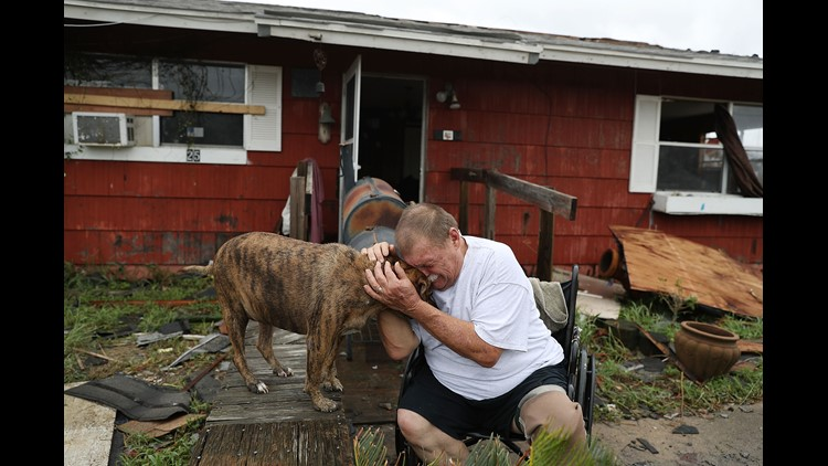 """Steve Culver cries with his dog Otis as he talks about what he said was the, """"most terrifying event in his life,"""" when Hurricane Harvey blew in and destroyed most of his home while he and his wife took shelter there in Rockport, Texas."""