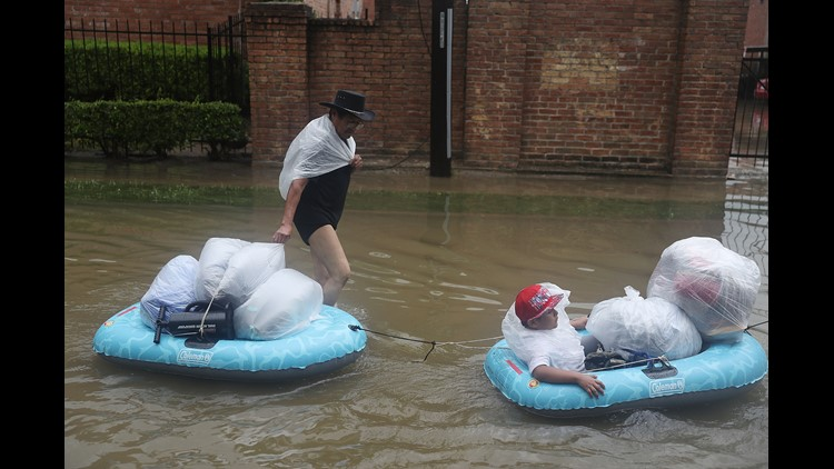 People walk down a flooded street as they evacuate their homes after the area was inundated with flooding from Hurricane Harvey on August 27, 2017 in Houston, Texas.