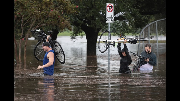 Residents navigate a flooded street that has been inundated with water from Hurricane Harvey on August 27, 2017 in Houston, Texas.