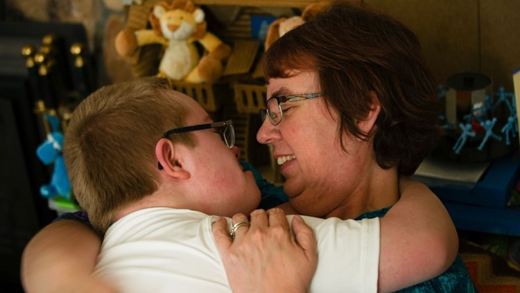Sandy Clayton hugs Sam, her 13-year-old son with Down syndrome, at their Federal Way home on April 5, 2018. (Photo: Taylor Mirfendereski | KING 5)