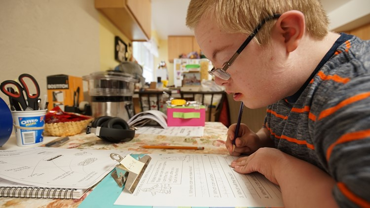 Sam Clayton, a 13-year-old with Down Syndrome, works on a reading assignment at his home. Clayton spends every school day in a self-contained classroom in the Federal Way School District, which is now conducting an audit of their special ed programs.