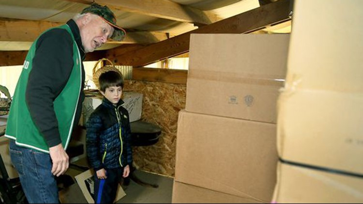 Zachary Darner, 8, and Ron Weekes with some of the boxes of toys donated by the Port Orchard Eagles Club. (Photo: Larry Steagall / Kitsap Sun)