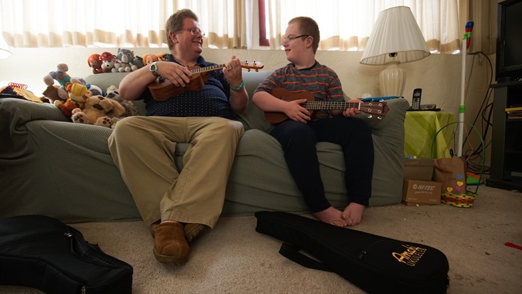 Sam Clayton, 13, practices the ukulele alongside his dad, Robert Clayton, at their Federal Way home on April 5, 2018. (Photo: Taylor Mirfendereski | KING 5)