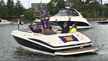 Husky football fans show their team spirit while sailing on the Montlake Cut