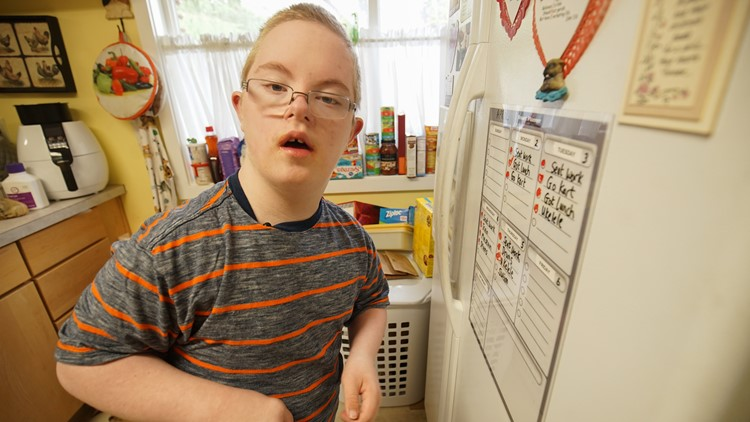 Sam Clayton, 13, poses for a photo after crossing an item off his to-do list on the fridge at his Federal Way home on April 5, 2018. (Photo: Taylor Mirfendereski | KING 5)