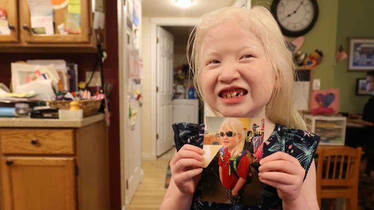 Sarah Carollo, 6, holds up a photo from her first day of first grade. (Photo: Taylor Mirfendereski | KING 5)