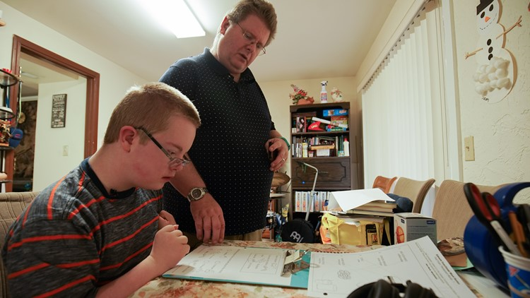 Rob Clayton motivates his 13-year-old son, Sam, to complete a school worksheet at their Federal Way home on April 5, 2018. (Photo; Taylor Mirfendereski | KING 5)