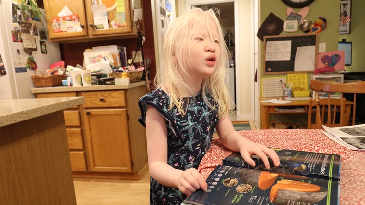 Sarah Carollo, a 6-year-old girl with autism, reads a book about space at her Sammamish home on May 13, 2018. (Photo: Taylor Mirfendereski | KING 5)