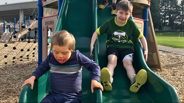Nate Paskins (left) goes down the slide with a friend during his first-ever play date in March 2018. (Provided photo)