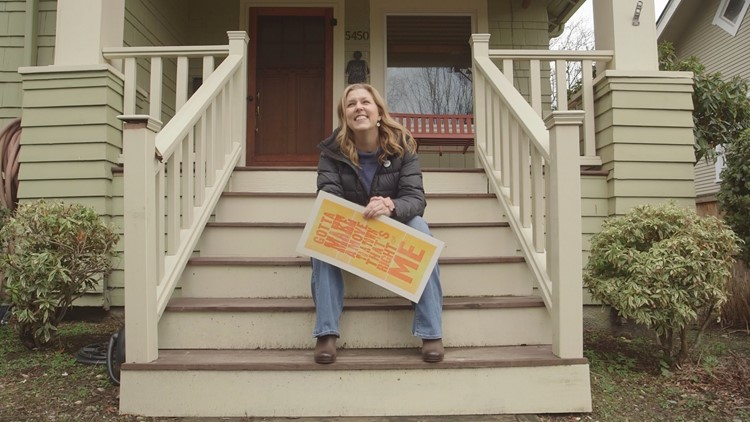 Amy Douglas sits on the steps of her historic craftsman home in West Seattle.