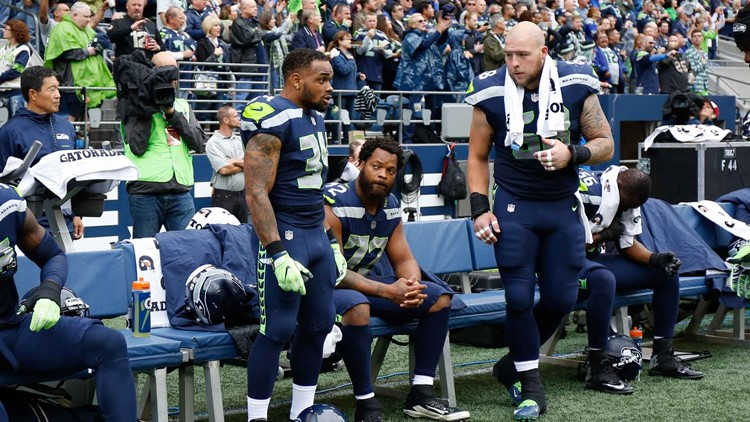 Defensive end Michael Bennett of the Seattle Seahawks, center, is joined by teammates Thomas Rawls and Justin Britt on the bench during the national anthem on September 17, 2017 in Seattle, Washington. (Photo by Otto Greule Jr/Getty Images)