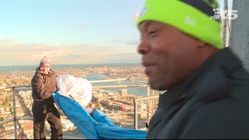 Lawyer Milloy raises the 12 flag atop Space Needle