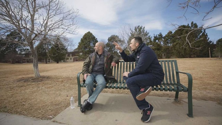 Christopher Zadnik sits with 9NEWS Investigator Jeremy Jojola on a bench as he talks about his various thoughts on the trails left by planes in the sky. (Photo: 9NEWS)