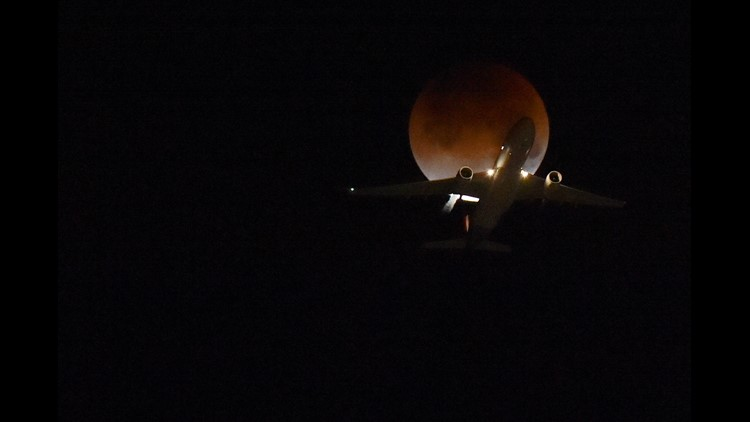 A plane flies passing the moon over Los Angeles, California, on January 31, 2018.