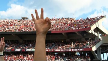 South Carolina fans raise threes on their hands in honor of WSU quarterback Tyler Hilinski